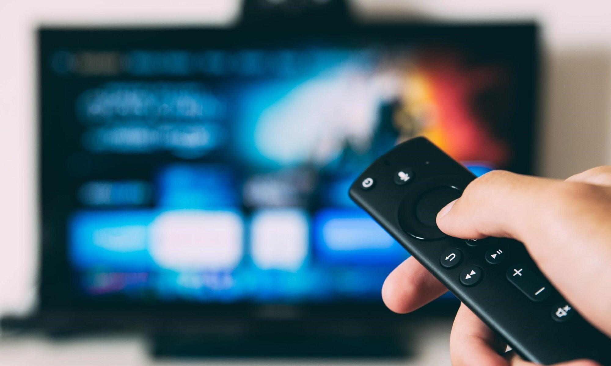 Hand mit Fernbedienung auf Fernseher gerichtet